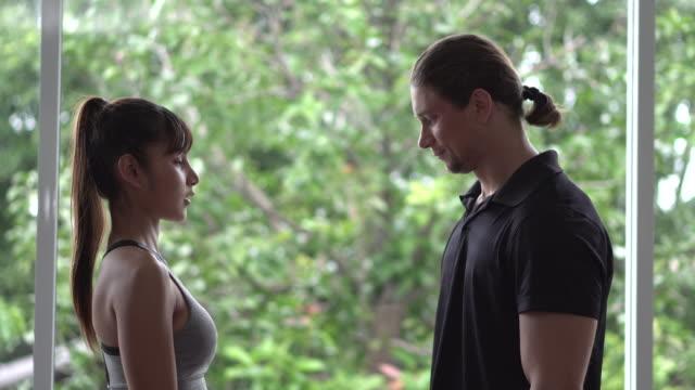 stockvideo's en b-roll-footage met medium shot vrouw training met trainer - bankdruktoestel