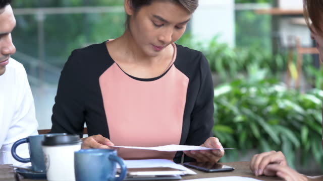 4K Medium shot young adult asian businessman and businesswoman freelance using digital tablet discussion business together at coffee shop outdoor. Teamwork young businessman and businesswoman working together.