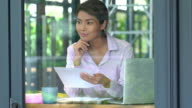 istock 4K Medium shot Young adult asian businesswoman sitting in coffee shop using digital laptop computer with internet wireless technology and document data for online stocks trading business. Businesswoman working outdoor concept. 1167346297