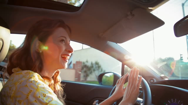 vídeos de stock e filmes b-roll de medium shot young woman driving and enjoying music - new