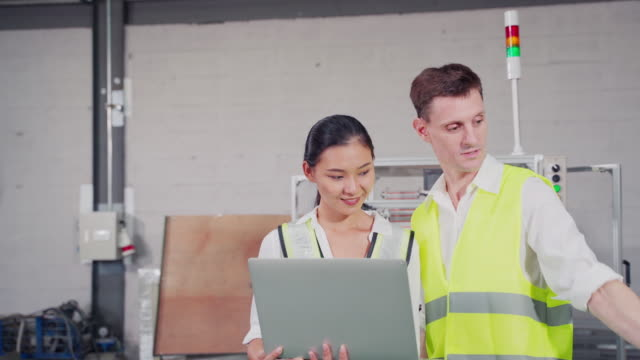 Medium shots of Male discuss with Female Engineers Industrial  Work on a Manufacturing Plant, They Discuss Project, Point in the Direction of the Machinery and Using Laptop. camera movement pan to subject,