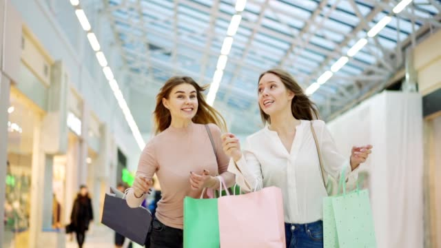 medium slow motion shot of two excited young women with shopping bags running along mall hurrying to make purchases on global sales day - black friday filmów i materiałów b-roll