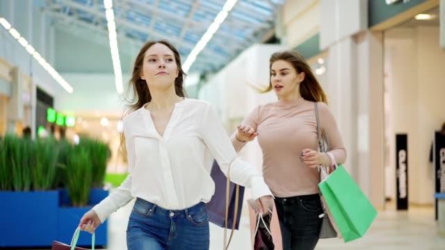stockvideo's en b-roll-footage met middellange slow-motion shot van twee opgewonden jonge vrouwen met boodschappentassen die langs mall slingelen om aankopen te doen op black friday. vrouw die haar rivaal uitduwt om als eerste in de winkel te zijn - black friday shop