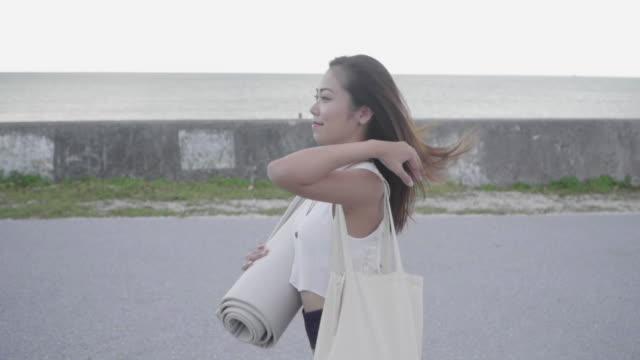 scatto di tracciamento medio di una donna millenaria che cammina con un tappetino da yoga e una borsa - materassino ginnico video stock e b–roll