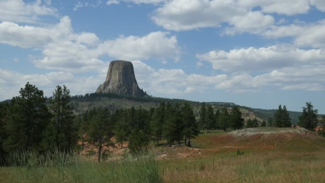 Medium wide shot with the Devils Tower or Bear Lodge Butte in the distance.