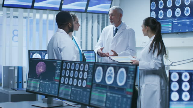 meeting of the team of medical scientists in the brain research laboratory. neurologists / neuroscientists having heated discussion surrounded by monitors showing ct, mri scans. - apparecchiatura medica video stock e b–roll