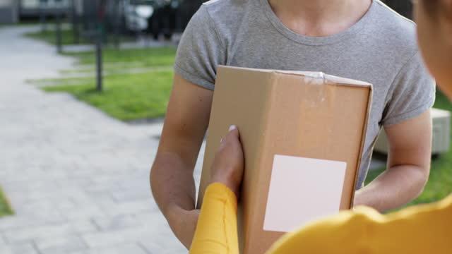 möte på gatan flicka leverans arbetstagare och kund. guy håller den mottagna beställningen i låda. face osynlig. - wine box bildbanksvideor och videomaterial från bakom kulisserna