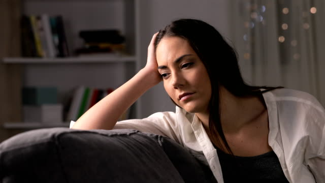 Melancholic woman looking away at home in the night