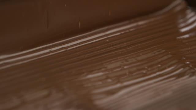 vídeos de stock e filmes b-roll de melted chocolate pouring in a candy factory - cacau em pó