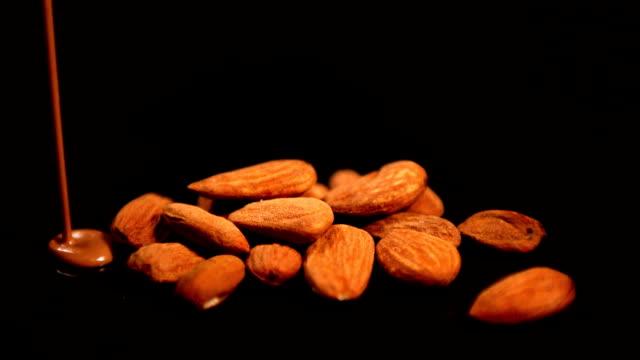 vídeos de stock e filmes b-roll de chocolate derretido verter sobre as amêndoas - amendoas