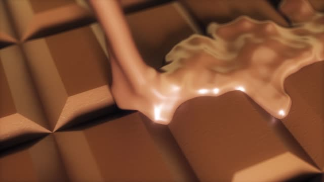 Melted chocolate pouring over chunks of chocolate in slow motion