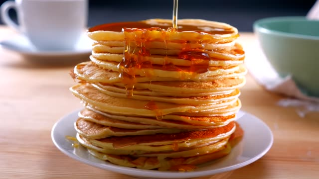 melted golden honey is doused on just cooked pancakes on table, ready to be eaten - pancake video stock e b–roll