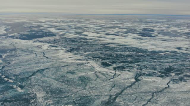 melting frozen ice on lake. - ghiaccio galleggiante video stock e b–roll