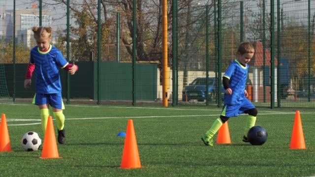 屋外でドリブルを学ぶサッカーチームのメンバー - サッカークラブ点の映像素材/bロール
