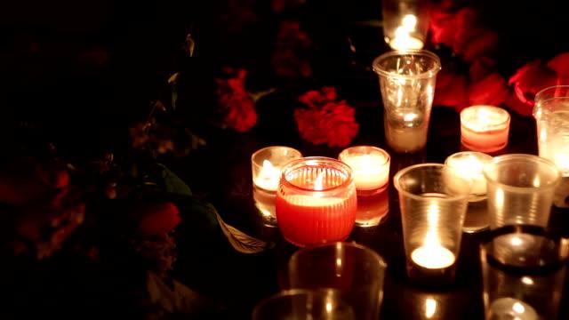 stockvideo's en b-roll-footage met memorial, bloemen en kaarsen in het geheugen van de doden door de terroristische aanslagen en militaire operaties. verdriet, compassie en tranen van mensen - funeral crying