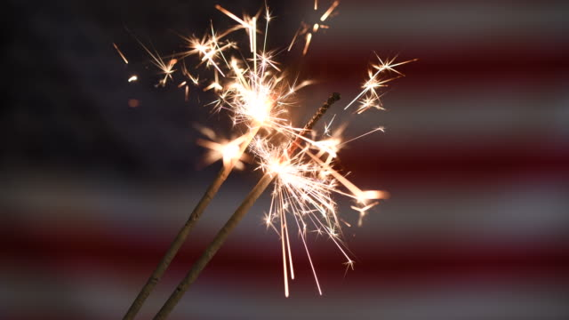 usa memorial or independence day concept with ignited sparkler in front of american flag - giorno dell'indipendenza video stock e b–roll
