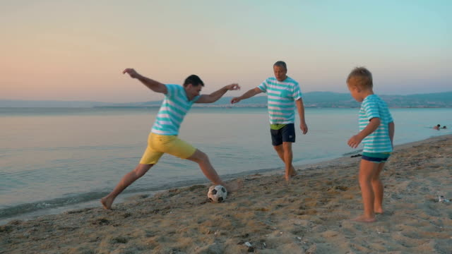Men and Boy Playing Football on the Beach video