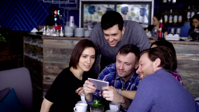 Men and women of middle age want to make a joint photo for memory, the company sits in a restaurant and expects its dinner, selected from the menu video