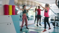 istock Men and Women Warming Up with Jumping Jacks at Gym 1202527308