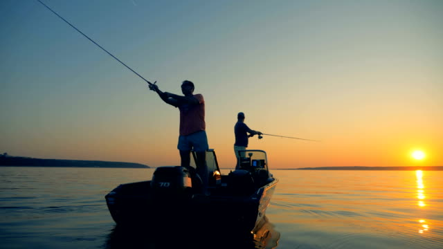 men are catching fish from an autoboat in the open water - fishing video stock e b–roll