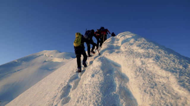 Men are climbing to the top of the mountain video