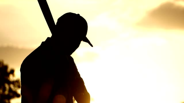 Men are hitting the baseball player with the sunset