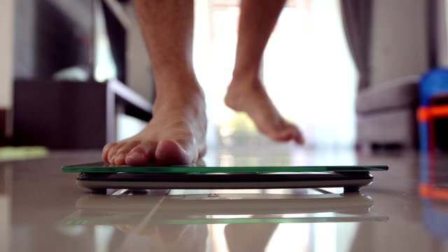 men barefoot legs stepping on flooring scales and jumps of the scale and starts dancing, celebrating weigh loss. - fare un passo video stock e b–roll
