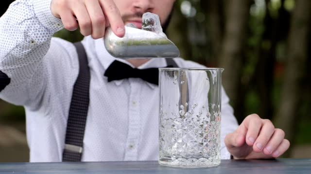 men barman adds ice cubes in glass for alcohol, barkeeper put ice cubes in glass at bar counter video