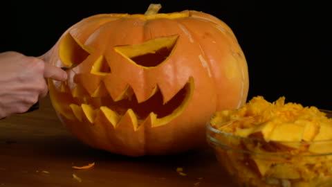 gli uomini intasano la zucca di jack o' lantern per la celebrazione di halloween. - decorazione festiva video stock e b–roll