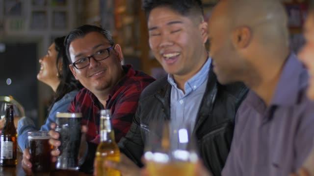 男性はスポーツバーで乾杯乾杯 - バーカウンター点の映像素材/bロール