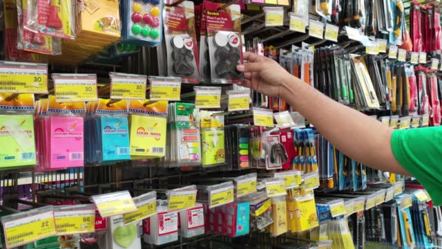 men choose items that they want to buy to use in department stores. - school supplies stock videos and b-roll footage