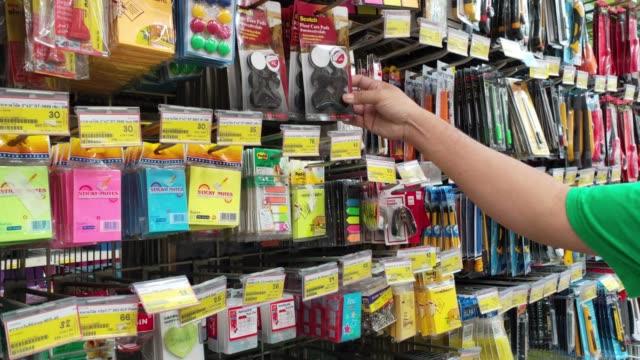 vidéos et rushes de les hommes choisissent les articles qu'ils veulent acheter à utiliser dans les grands magasins. - fournitures scolaires