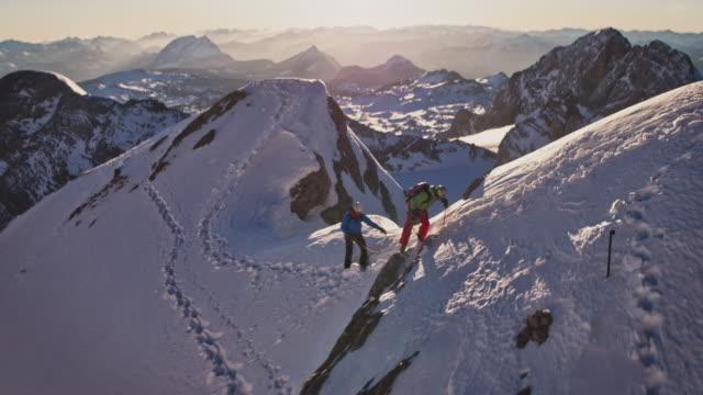 män klättring snötäckta berg under soliga dagar - bergsrygg bildbanksvideor och videomaterial från bakom kulisserna