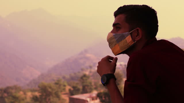 Men covering his face with pollution mask for protection against COVID-19 video