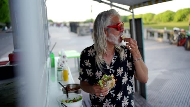 vídeos de stock, filmes e b-roll de homens que comem o alimento do caminhão do alimento - cachorro quente