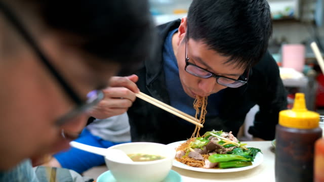 Men eating Tossed Noodle with Pork and Boiled Pork Liver, Hong Kong, Chinese Food video