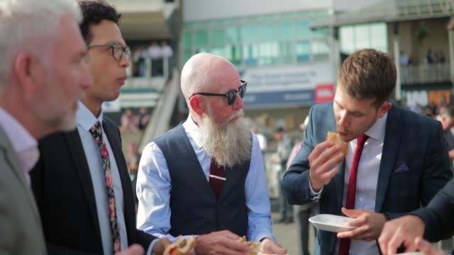 stockvideo's en b-roll-footage met mannen genieten van hamburger, chips en bier buiten - foodtruck
