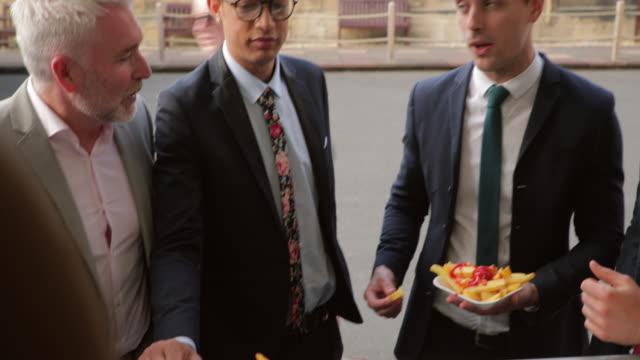 männer genießen speisen aus einem imbisswagen - schnellkost stock-videos und b-roll-filmmaterial