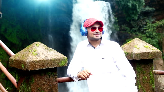 Men enjoying music near waterfall Full HD : - Young man standing near waterfall in the nature, Goa. He is listening songs by using headphones. bluetooth stock videos & royalty-free footage