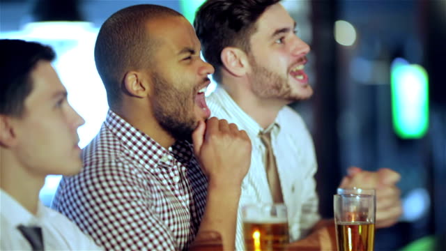 男性のサッカーファンが観戦にテレビとドリンク、ビール - バーカウンター点の映像素材/bロール