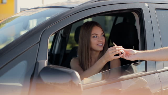 men giving keys to a young woman sitting inside the car video