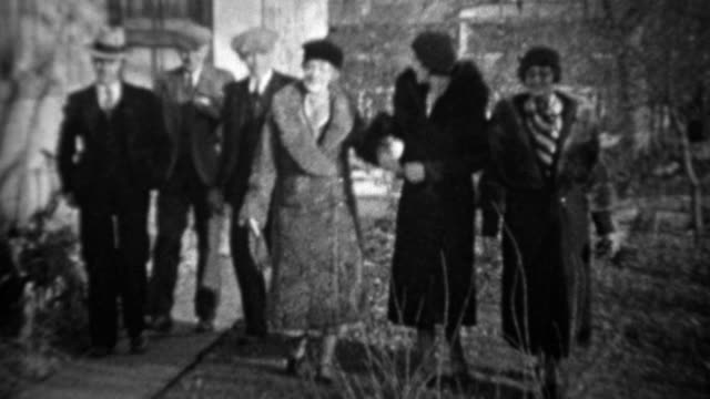 1933: Men greeting women tipping cap bowing to pretty wifes.
