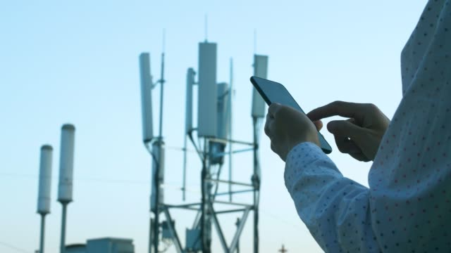 Men hand using phone with 5G telecommunications station tower background
