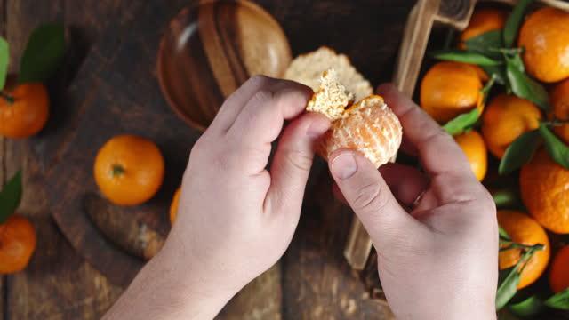 Men hands remove the peel from tangerine.