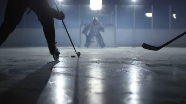 vidéos et rushes de hommes frappant la rondelle vers le filet - hockey sur glace