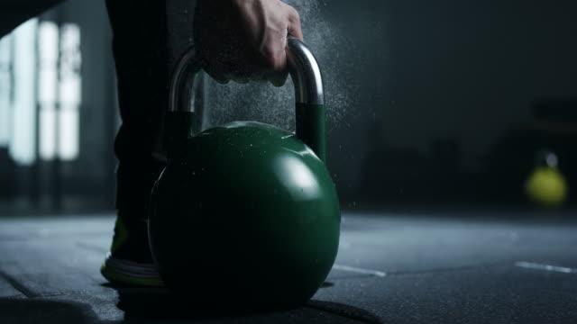 Men holding kettlebell in gym video