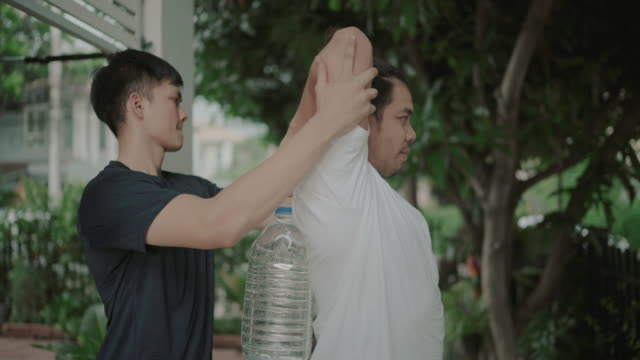 Men holding plastic water gallon instead of gym weights at home exercise