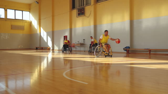 Men in wheelchair playing basketball on the court