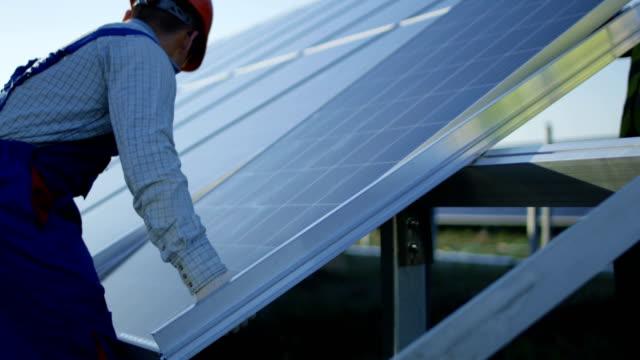 Men installing solar panel outdoors