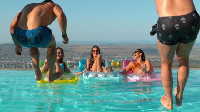 vídeos de stock, filmes e b-roll de os homens que saltam na água e nas mulheres em colchões, ultra slow motion - inflável